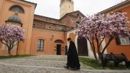 Ein Priester mit Mundschutz geht durch den Kirchhof in Codogno.