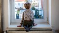 Corona-Kindheit: Ein vierjähriger Junge aus Niedersachsen schaut während des zweiten Lockdowns aus dem Fenster.