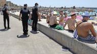 Abstand, bitte!  Polizisten patrouillieren am Strand von Arenal auf Mallorca.