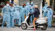 Vietnamesische Polizisten in Schutzkleidung vor einem provisorischen Zentrum für Corona-Tests in Hanoi