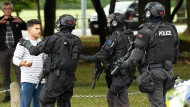 Mitglieder einer Spezialeinheit der Polizei (AOS) drängen Schaulustige vor einer Moschee in Christchurch zurück.