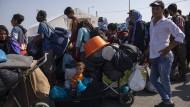Migranten stehen am Donnerstag vor dem Eingang zum Zeltlager von Kara Tepe Schlange.