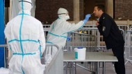 Im Kampf gegen das Virus: Einem Mitarbeiter der Berufsfeuerwehr Köln wird im dritten Infektionsschutzzentrum der Stadt mit einem Stäbchen ein Abstrich für einen Test genommen.