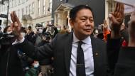 Kyaw Zwar Minn zeigt am Donnerstag in London den Drei-Finger-Gruß der Opposition in Myanmar.