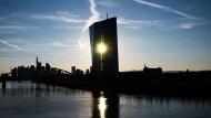 Die Sonne scheint zwischen den beiden Gebäudehälften der Europäischen Zentralbank hindurch.