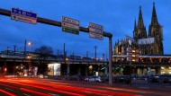 Autos fahren im morgendlichen Berufsverkehr am Kölner Dom vorbei.