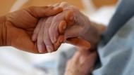 Eine Pflegerin hält die Hand.