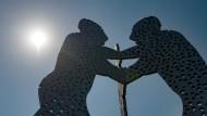 """Die Sonne strahlt neben dem Monumentalkunstwerk """"Molecule Man"""" des Bildhauers Jonathan Borofsky."""