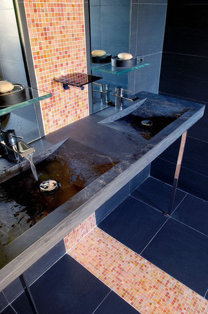 https www living4media com images 11163754 dark stone counter with integrated sinks and strip of bright mosaic tiles in modern bathroom