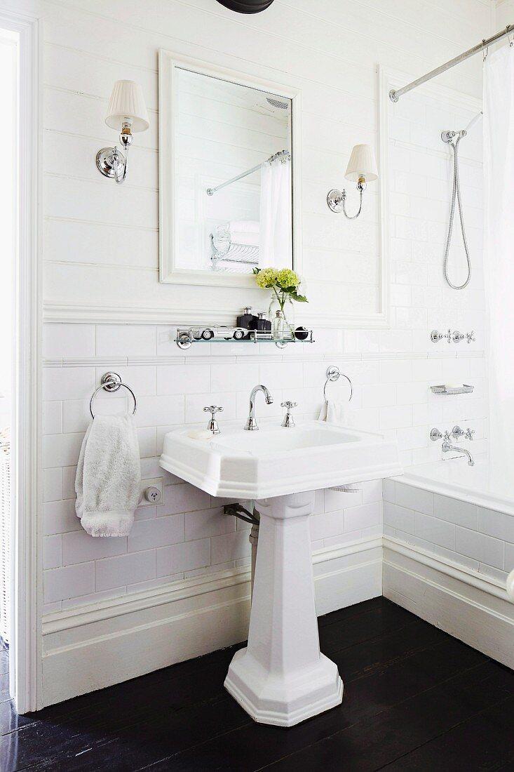 https www living4media com images 11276936 vintage pedestal sink on dark wooden floor framed mirror and symmetrical lamps on white wooden wall in