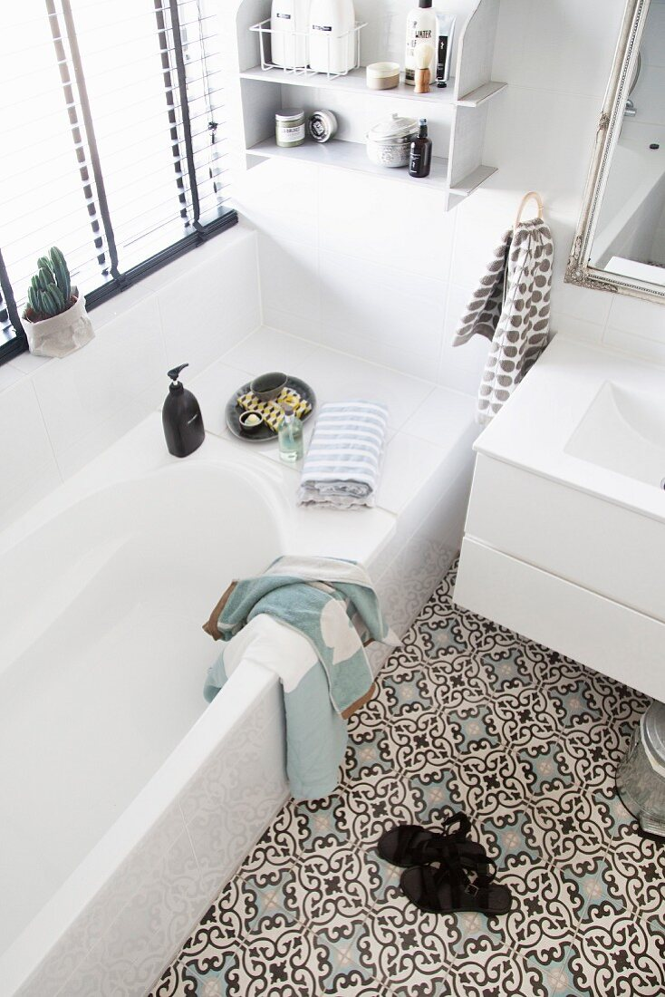 https www living4media com images 11378268 white bathroom with moroccan style ornamental floor tiles and wall mounted shelves above bathtub