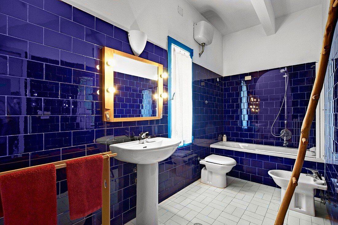 https www living4media com images 11393580 glossy ultramarine wall tiles in mediterranean style bathroom with bathtub pedestal sink and bidet
