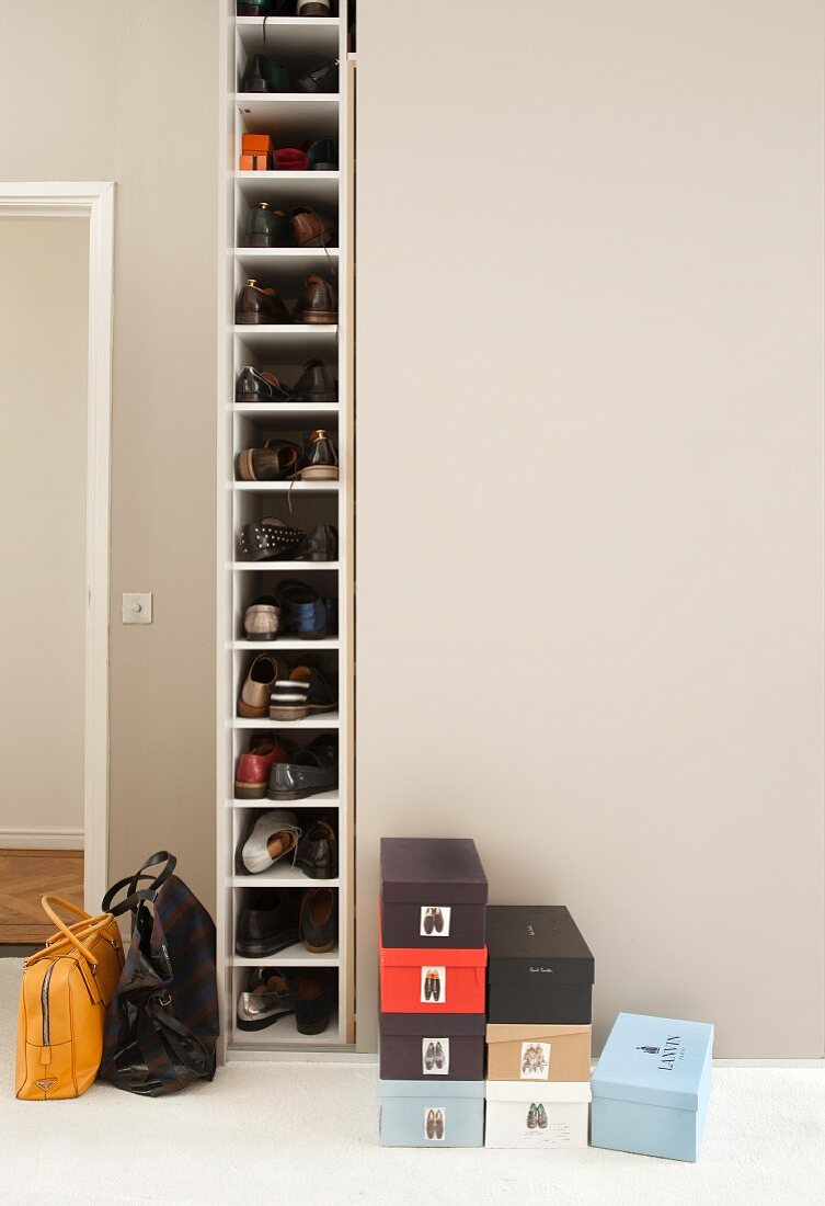 https www living4media com images 12086874 many shoes in tall narrow shoe cabinet next to stacked shoeboxes