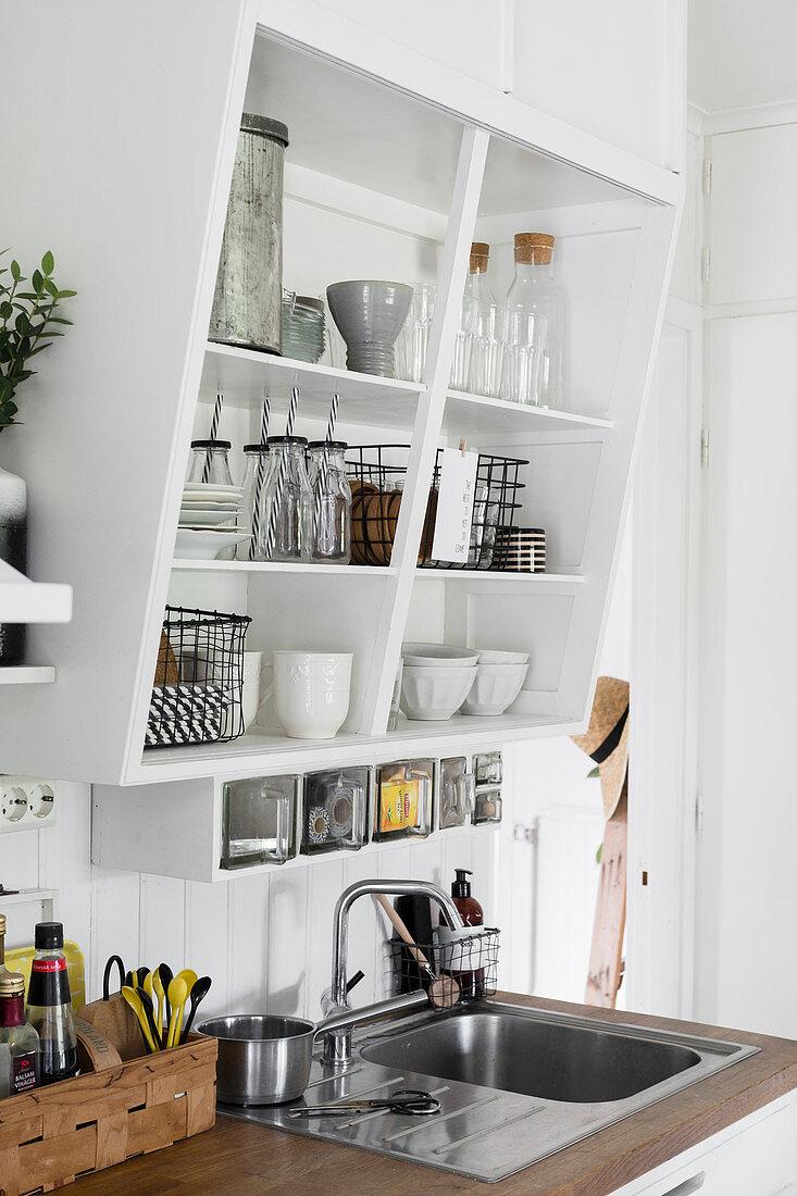 https www living4media com images 13190354 crockery and glasses on slanted kitchen shelves above sink
