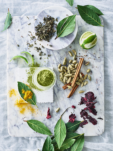 A still life with spices, lime, matcha powder and tea