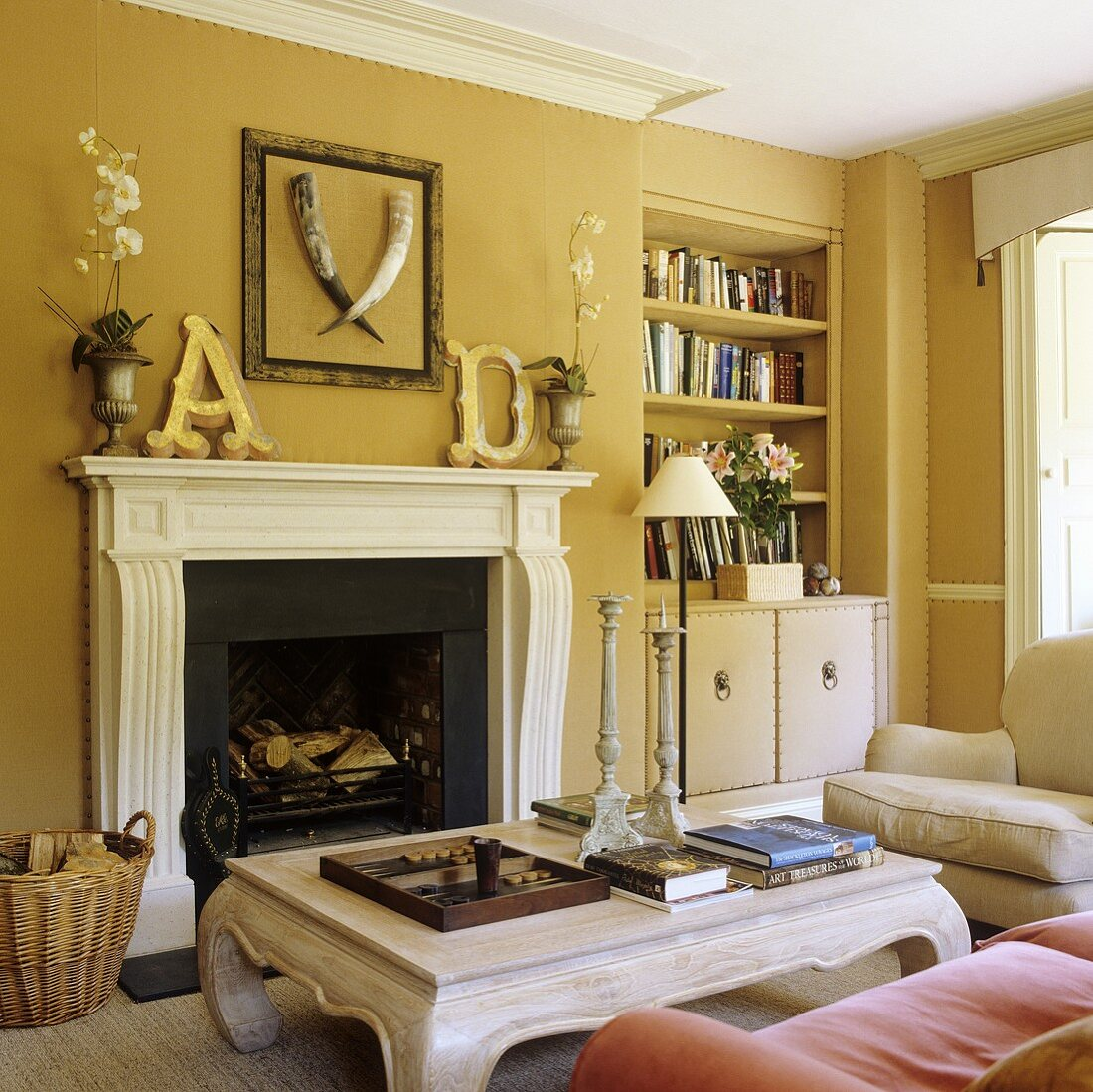 https www living4media com images 00706395 a living room with yellow walls and a coffee table in front of a fireplace and a built in shelf