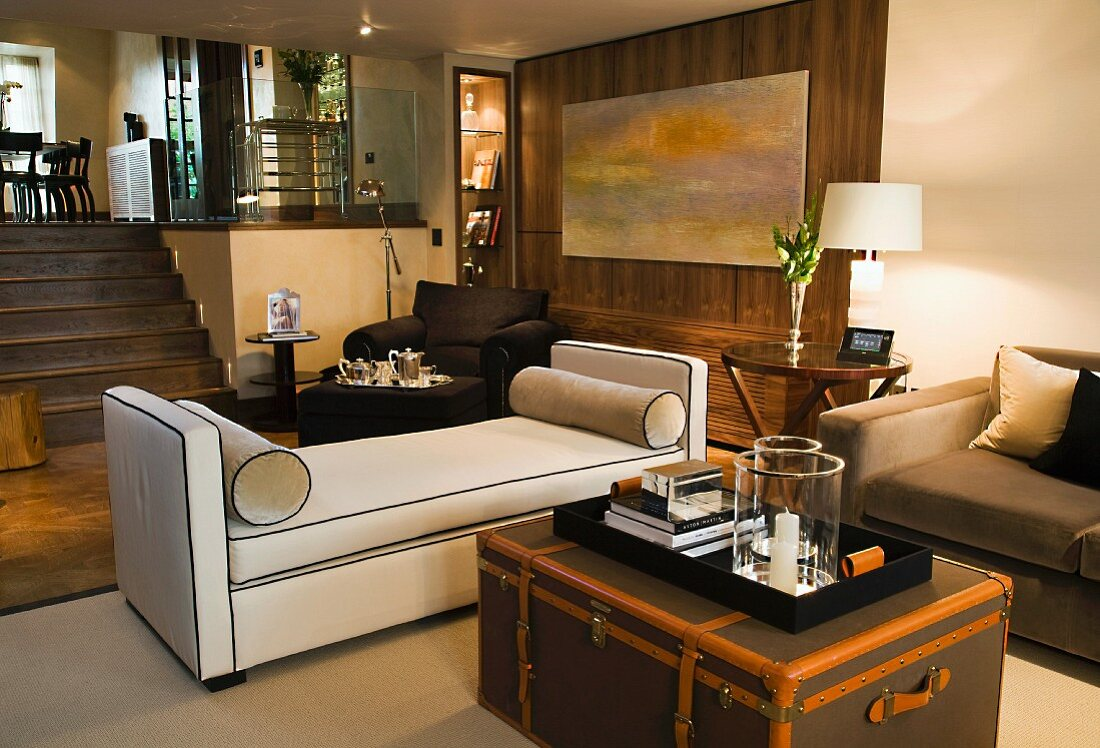 https www living4media com images 11016189 tray on antique trunk in front of light upholstered couch in modern split level living space