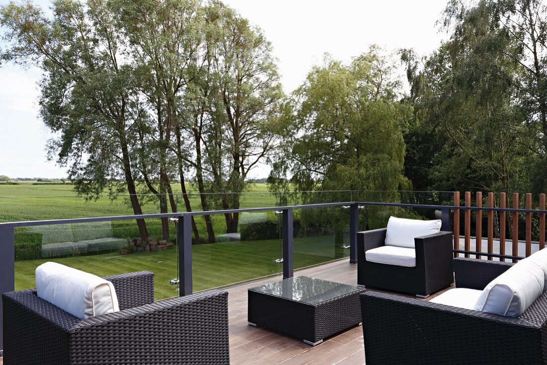 https www living4media com images 11436347 black rattan outdoor furniture with white cushions on terrace with view across landscape