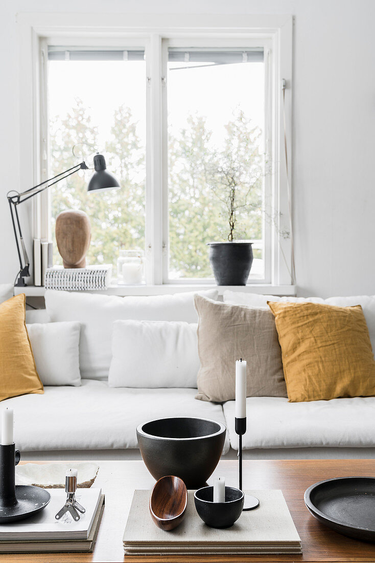 https www living4media com images 12611527 ornaments on coffee table in front of sofa with mustard yellow cushions below window