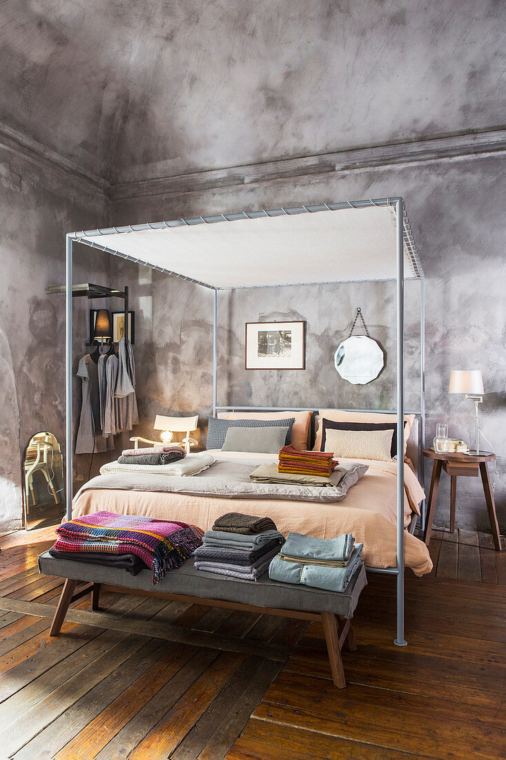 https www living4media com images 12998495 modern metal four poster bed with blankets and bed linen on bedroom bench at foot