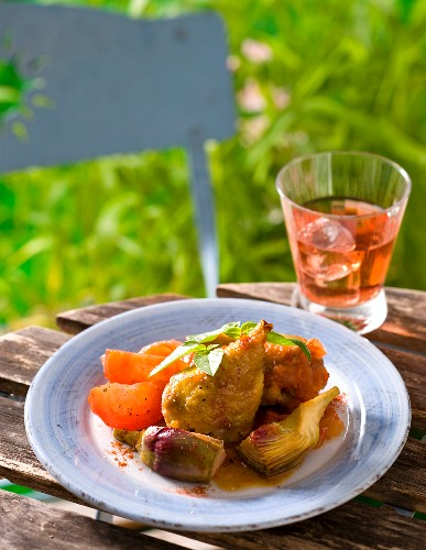 Roasted chicken legs with artichokes and tomatoes on a table outside