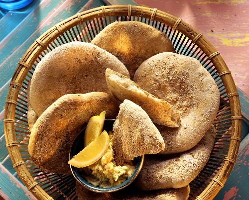 Arabic flat bread in bread basket with spread