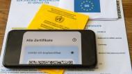 Ein Impfpass und ein Smartphone, auf dem die App CovPass läuft, liegen auf einem Impfzertifikat, das von einer Apotheke ausgestellt wurde.