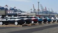 Stotternder Weltmotor: Große Anschaffungen wie Autos dürften später nachgeholt werden. Autos stehen in Bremerhaven vor der Verladung auf Schiffe Schlange.