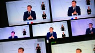 Präsident Emmanuel Macron ist auf mehreren Bildschirmen zu sehen, während er seine Fernsehansprache hält.
