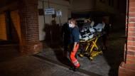 Sanitäter verlassen das Gelände der Klinik, wo vier Menschen getötet wurden.