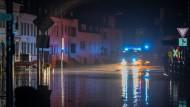 Ein Feuerwehrfahrzeug fährt durch eine von dem Fluss Kyll überflutete Bahnhofstrasse in Kordel in Rheinland-Pfalz.
