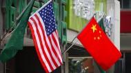 Die amerikanische und chinesische Flagge wehen vor einem Hotel in Peking.