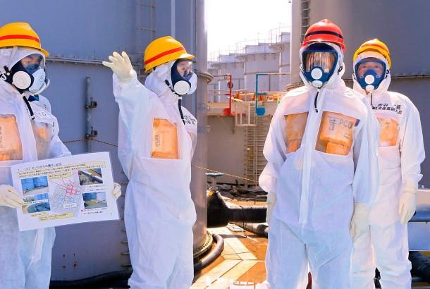 Japans Premierminister Shinzo Abe (mit dem roten Helm) begutachtet die Wassertanks.