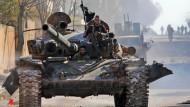Von der Türkei unterstützte syrische Rebellen fahren in Idlib im Nordwesten Syriens mit einem Panzer.