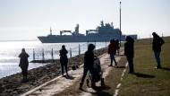"""Mit ausreichend Abstand zueinander beobachten Menschen in Wilhelmshaven das Auslaufen des Einsatzgruppenversorgers """"Berlin""""."""
