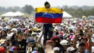 Ein Kind trägt eine venezolanische Flagge bei dem Benefitkonzert Venezuela Aid Live auf der kolumbianischen Seite der Grenzbrücke Tienditas.