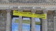 Greenpeace-Aktivisten hängen ein Banner vor den Reichstag