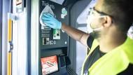 Eine Reinigungskraft desinfiziert einen Ticketautomaten in der Rheinbahn