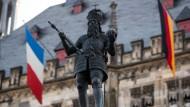 Eine deutsche und eine französische Flagge hängen hinter der Figur Karls des Großen am Rathaus von Aachen.
