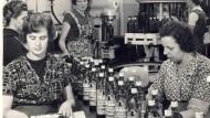 Flaschen werden auf einer historischen Aufnahme des Unternehmens Schwarze und Schlichte per Hand verpackt.