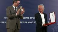 Peter Handke (r), Autor aus Österreich, nimmt bei einem Festakt den Karadjordje-Orden vom Aleksandar Vucic, Präsident von Serbien, entgegen.