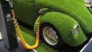 Ein grüner VW Käfer steht auf der Hannover Messe an einer Elektrotankstelle.
