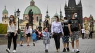 Auf der Prager Karlsbrücke wappnen sich Passanten gegen Corona. Mancher sieht derweil eine neue Bedrohung aufkommen: Ist die Landessprache in Gefahr?