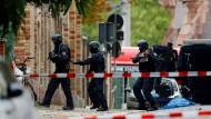 Polizeibeamte sichern in Halle den Tatort am jüdischen Friedhof