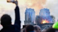 Fassungslos fotografiert ein Passant am Montagabend den Brand der Kathedrale Notre-Dame, einem der berühmtesten Wahrzeichen der Welt