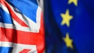 Eine Flagge der Europäischen Union und eine Flagge von Großbritannien wehen vor dem britischen Parlament in Westminster.