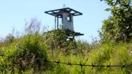 Bei der Marterstätte blüht die Natur: ein verfallener Wachturm und Stacheldraht vor einem ehemaligen Straflager in Sibirien