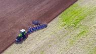 Ein Landwirt in Mecklenburg-Vorpommern pflügt ein abgeerntetes Feld und bereitet es für die Neubestellung vor.