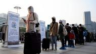 Vor einem Bahnhof in Wuhan warten Reisende in einer Schlange, um die Stadt zu verlassen.
