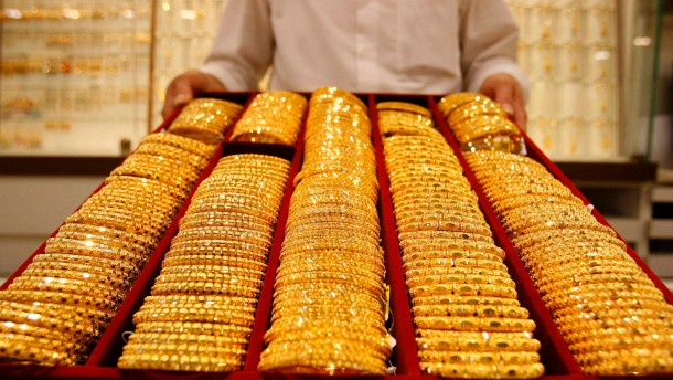 Shop attendant displays a tray of gold bangles for the camera at a jewellery story in Singapore